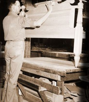 A black and white image of a man working on a carpentry project